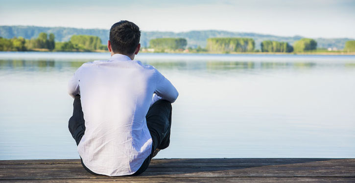 Image of man sitting on a dock thinking about trauma therapy